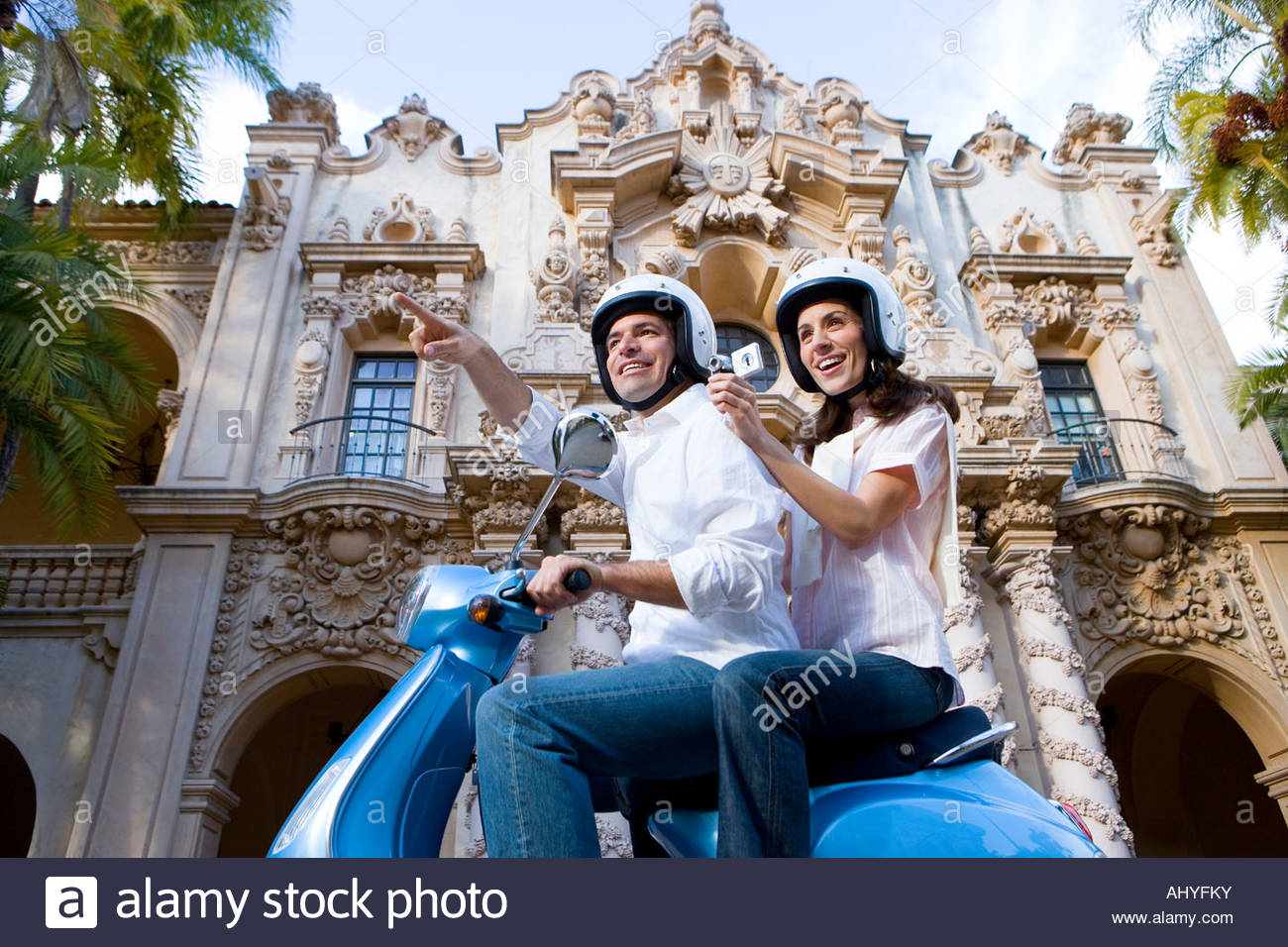 Couple riding on blue motor scooter, woman filming with video camera, smiling, side view, low angle view - Stock Image