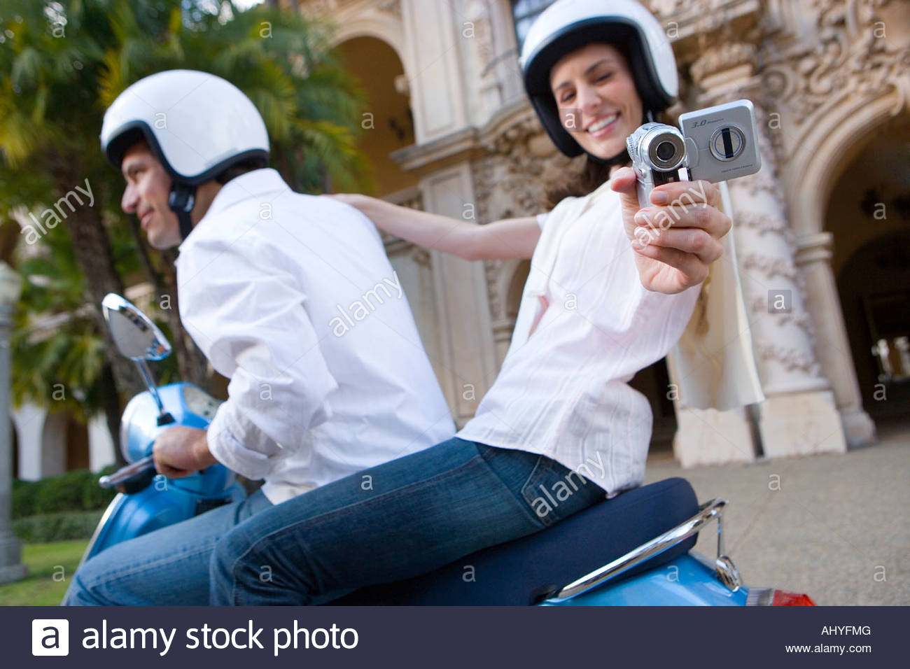 Couple riding on blue motor scooter, woman filming with video camera, smiling, side view, portrait tilt - Stock Image