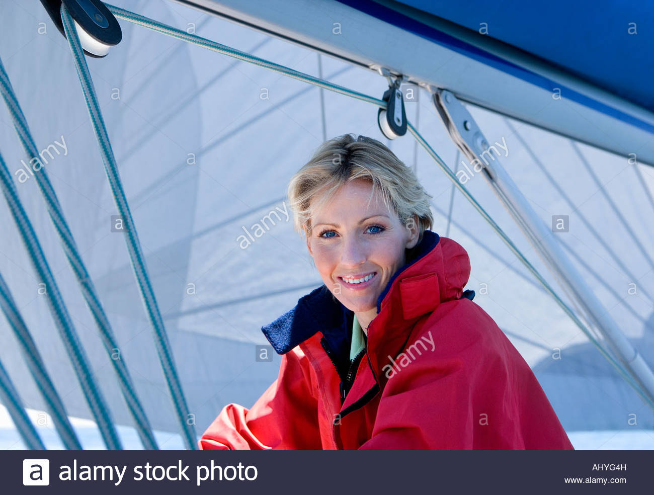 Woman in red jacket sitting on deck of sailing boat below sail, smiling, side view, portrait - Stock Image