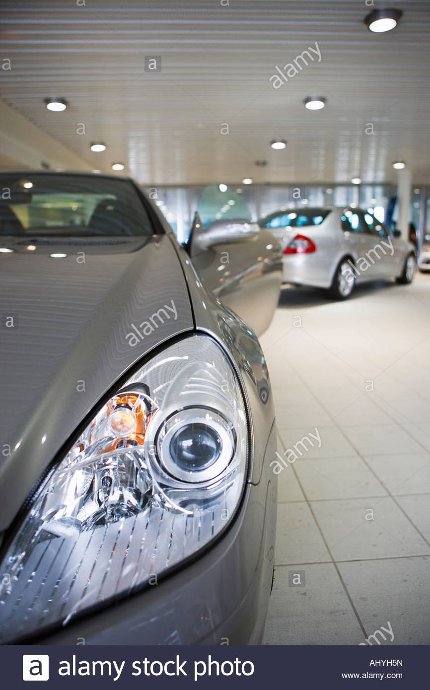 New silver saloon and convertible cars parked in large showroom, focus on foreground - Stock Image
