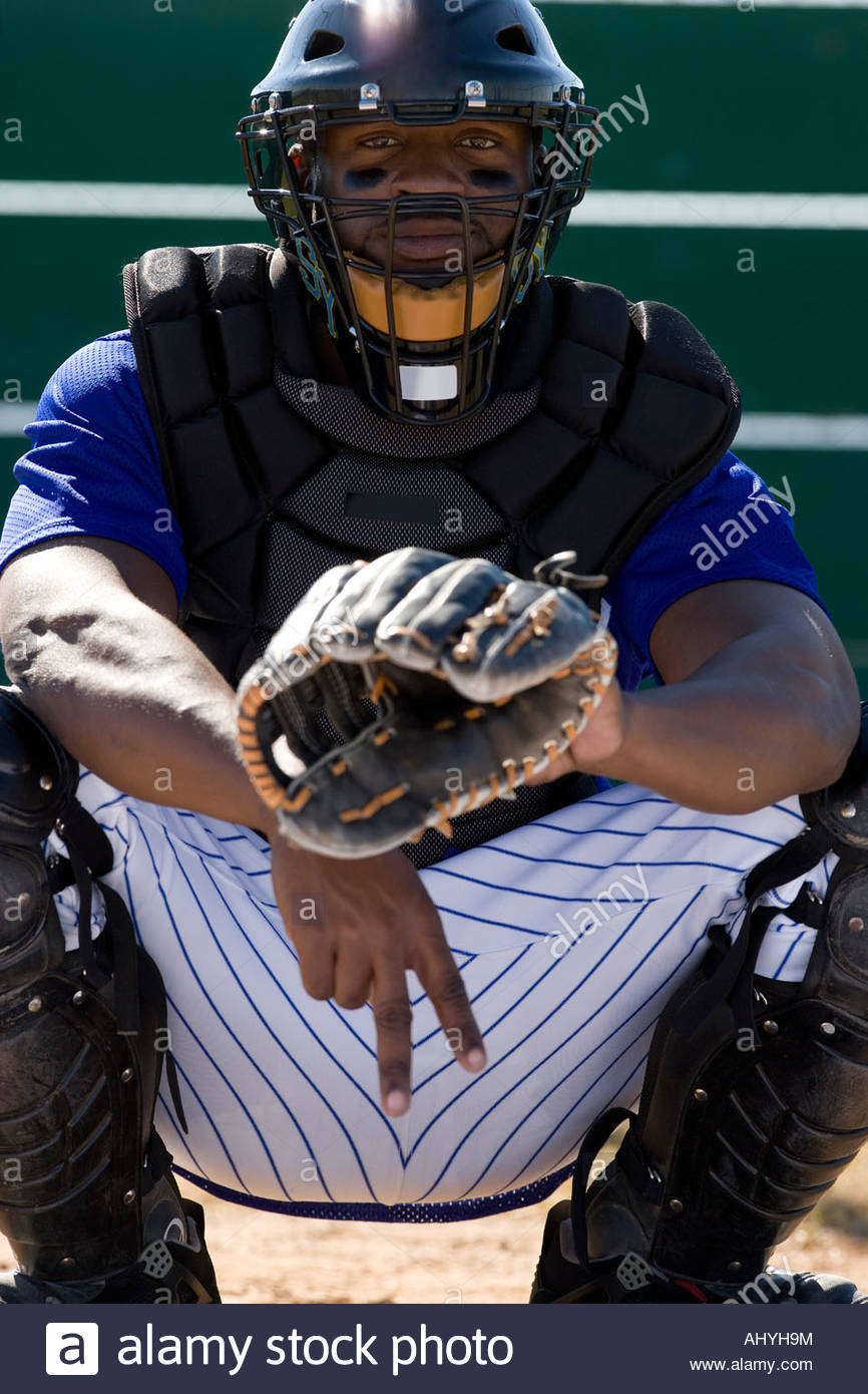 Baseball catcher crouching on pitch, making secret signal with fingers, front view, portrait - Stock Image