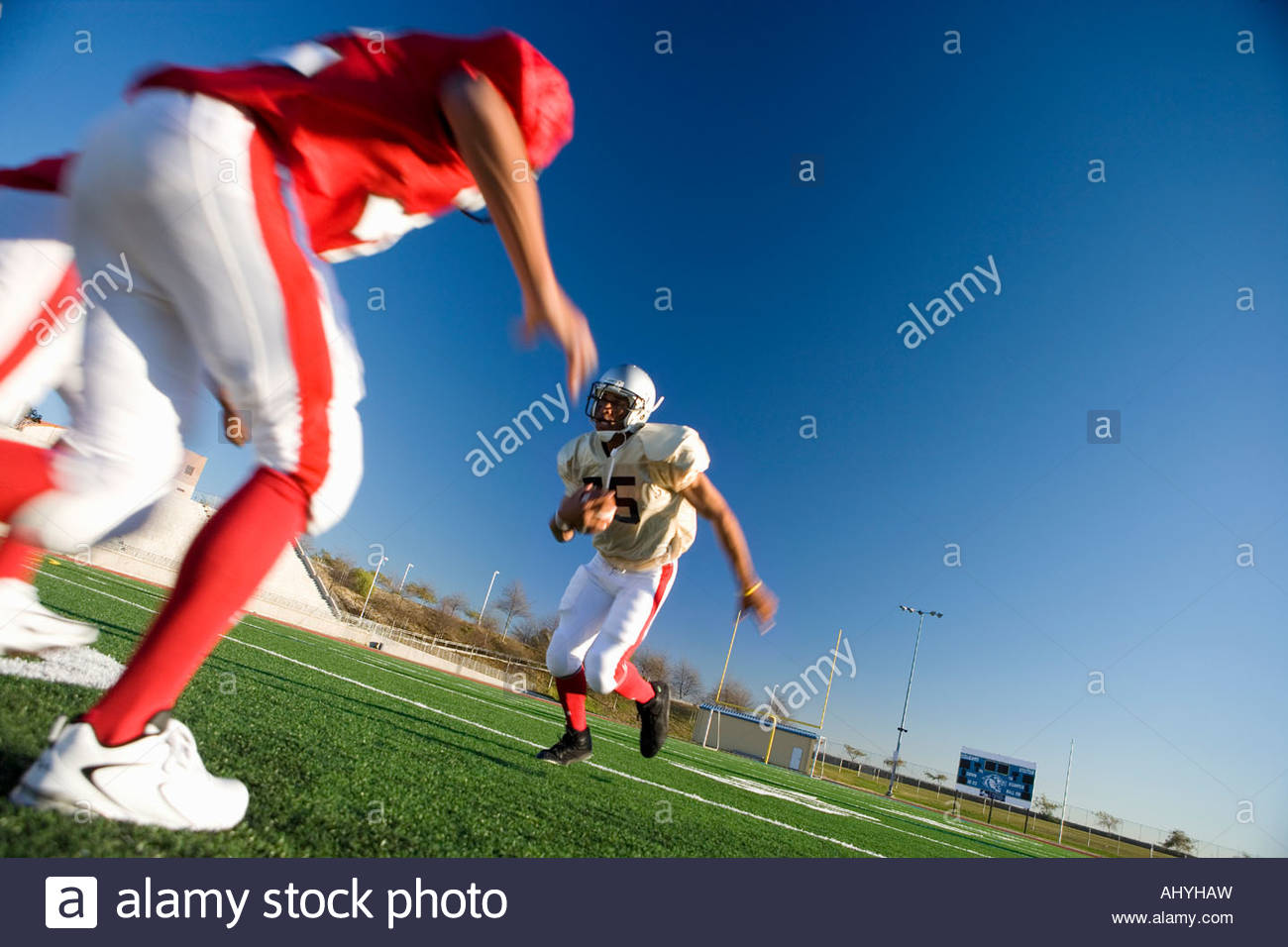 American football player running with ball at opposing team during competitive game surface level, tilt - Stock Image