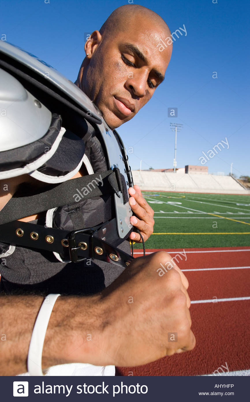 American football player adjusting protective shoulder pad strap pitchside on sports track, side view - Stock Image