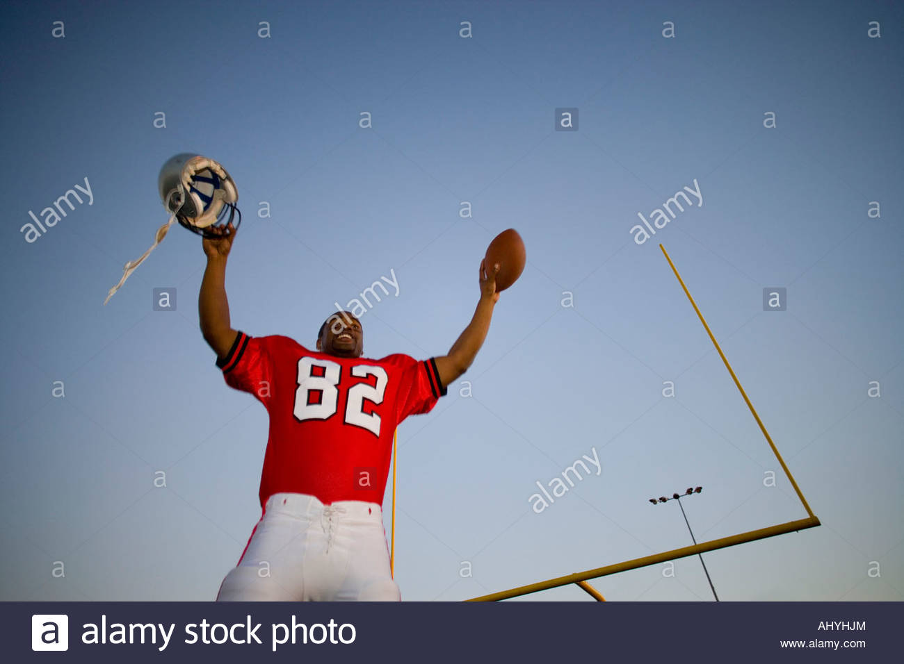 American football player, in red strip, celebrating victory on pitch at sunset, arms up, holding ball and protective - Stock Image