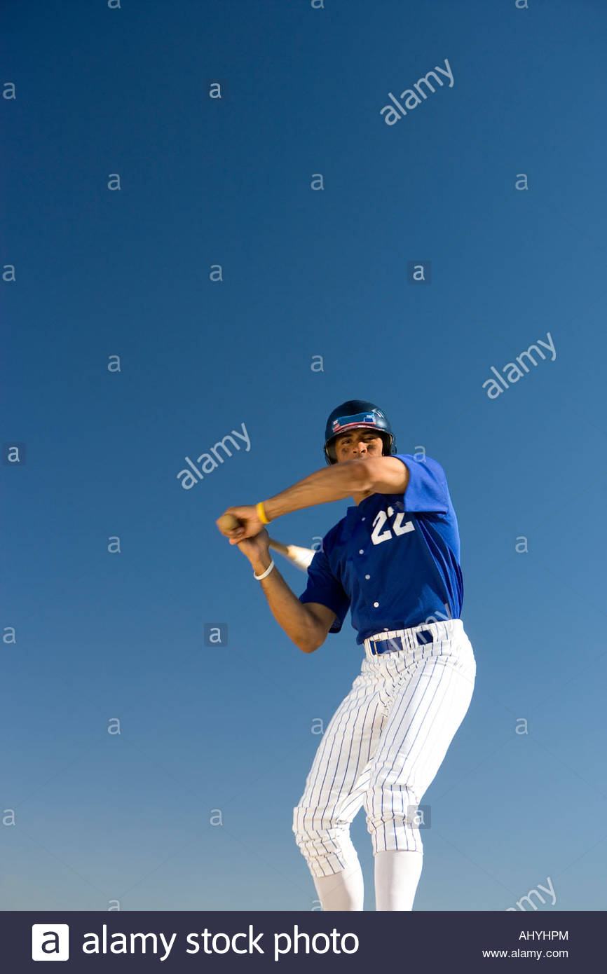 Baseball batter standing against clear blue sky, preparing to hit ball, front view, low angle view - Stock Image