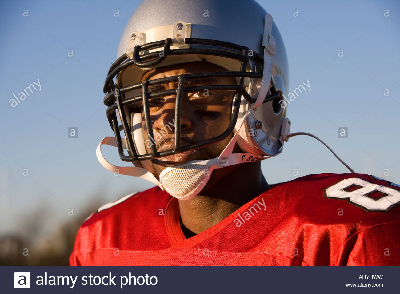 American football player wearing red football strip and protective helmet, close-up, portrait - Stock Image
