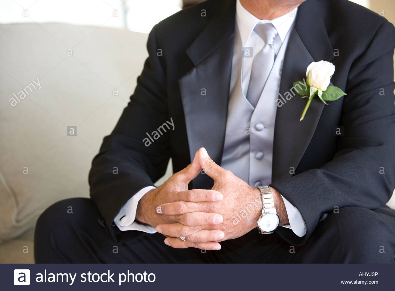 Senior groom, in formalwear, sitting on chair at wedding, thumbs pressed together, mid-section - Stock Image