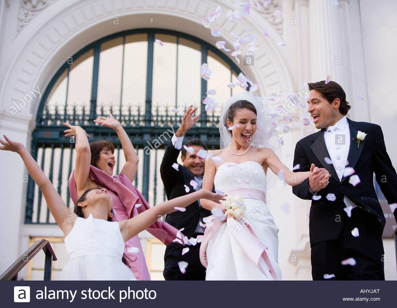 Bride and groom descending steps outside church, wedding guests throwing confetti, smiling, low angle view - Stock Image