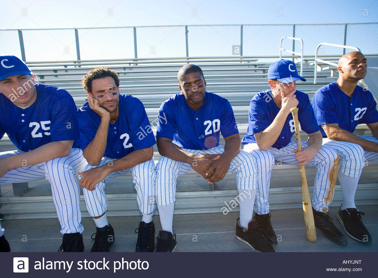 Dejected baseball team sitting on bench in stand during competitive baseball game, looking gloomy, front view backlit - Stock Image