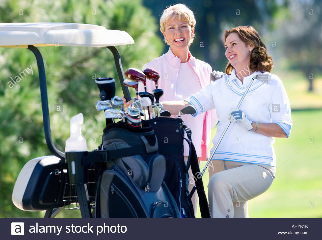 Two mature women standing beside parked golf buggy, playing golf, brunette holding golf club, smiling, portrait - Stock Image