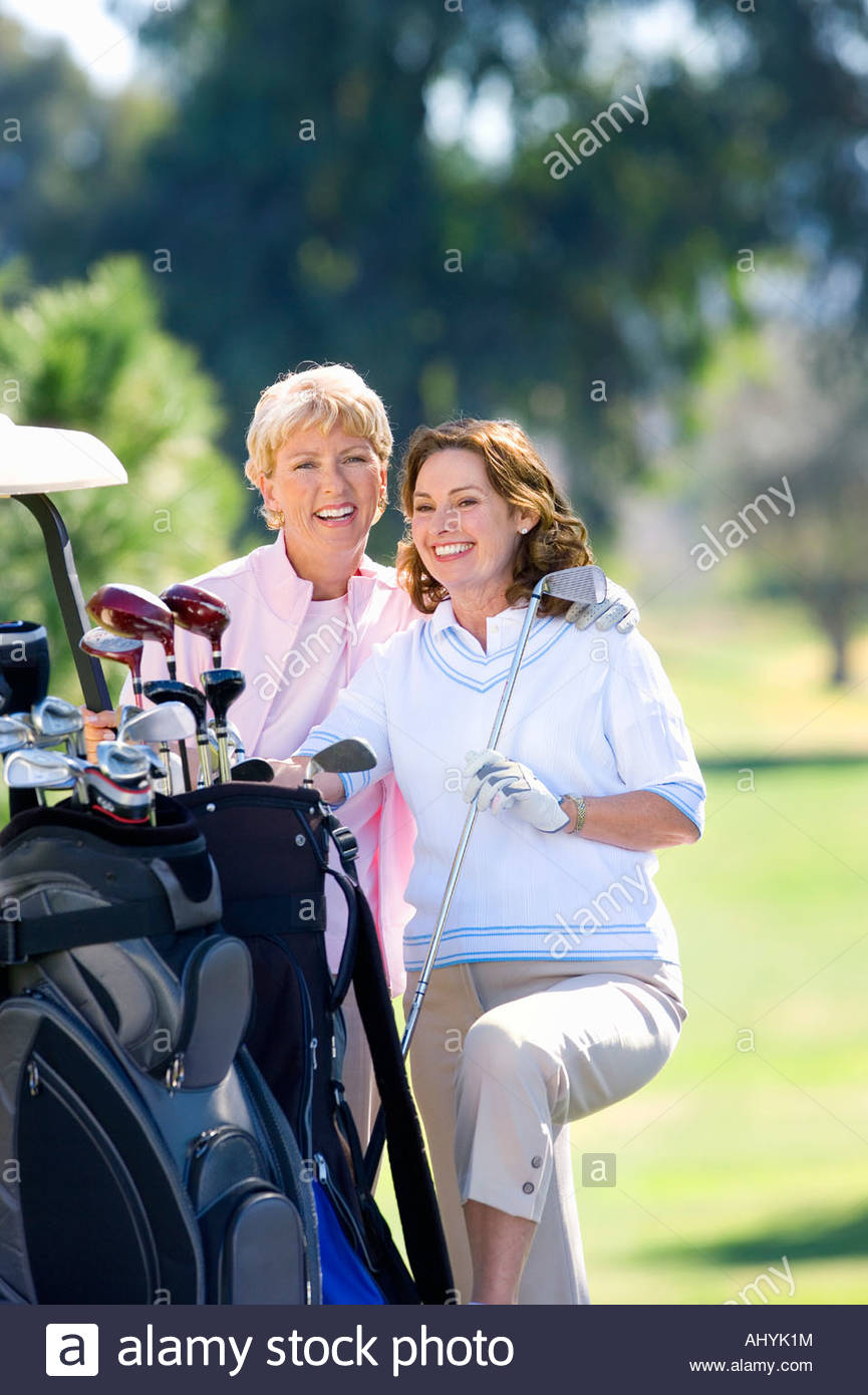 Two mature women standing beside parked golf buggy, playing golf, brunette holding golf club, laughing, portrait - Stock Image