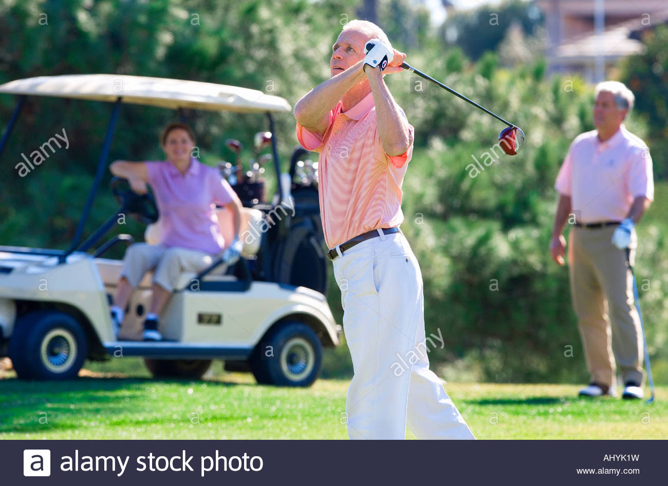 Three mature adults playing golf, mature man in polo shirt driving golf ball from tee, mature couple watching from - Stock Image