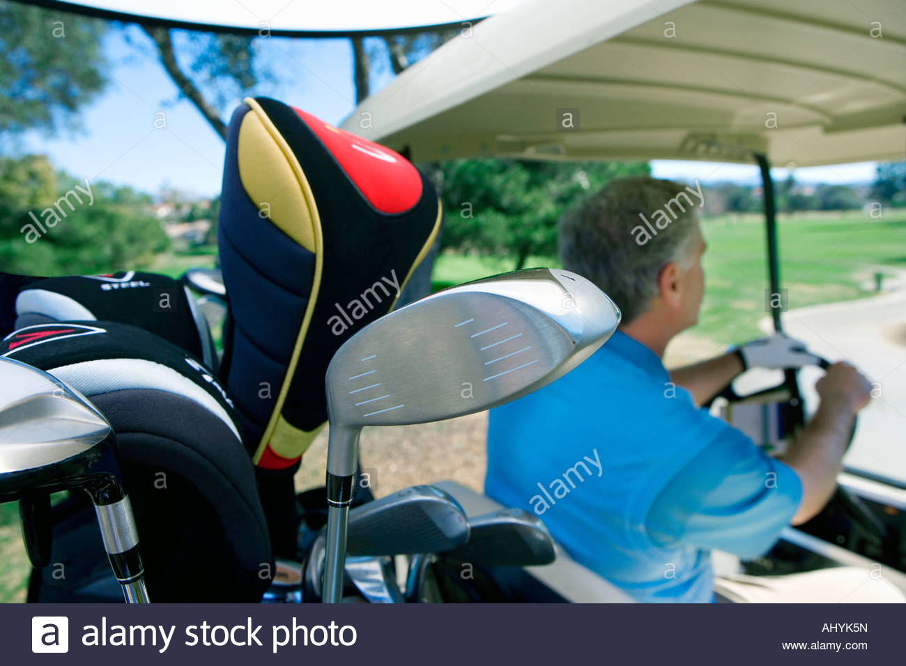 Mature man driving golf buggy on golf course, focus on golf clubs and bag in foreground, side view - Stock Image