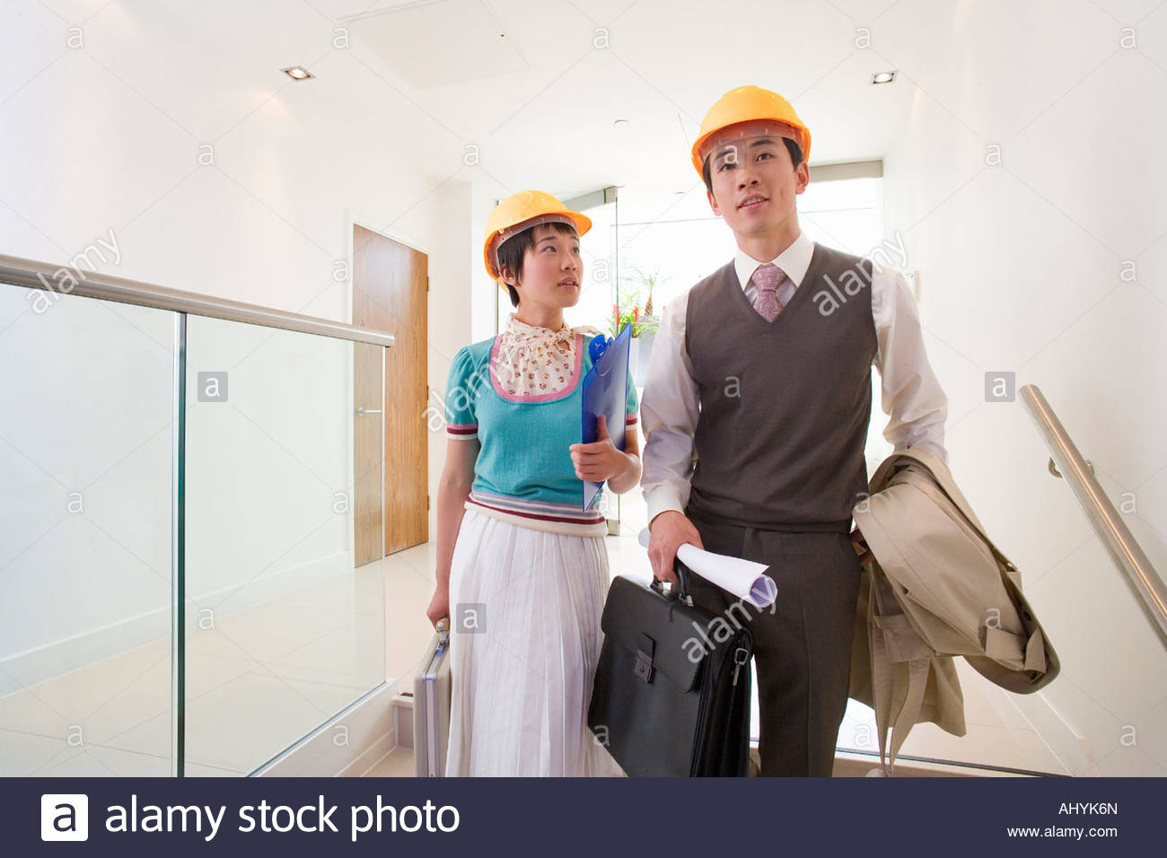 20'S Japanese businessman and woman wearing hard hats walking through the office, - Stock Image