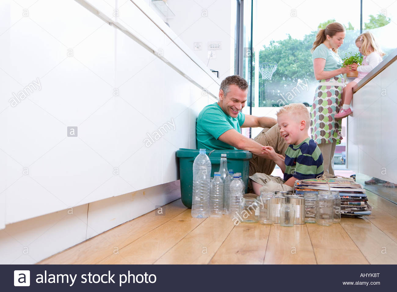 30's couple, girl and boy children aged 6 in kitchen with bottles, tins and newspapers for recycling with green - Stock Image
