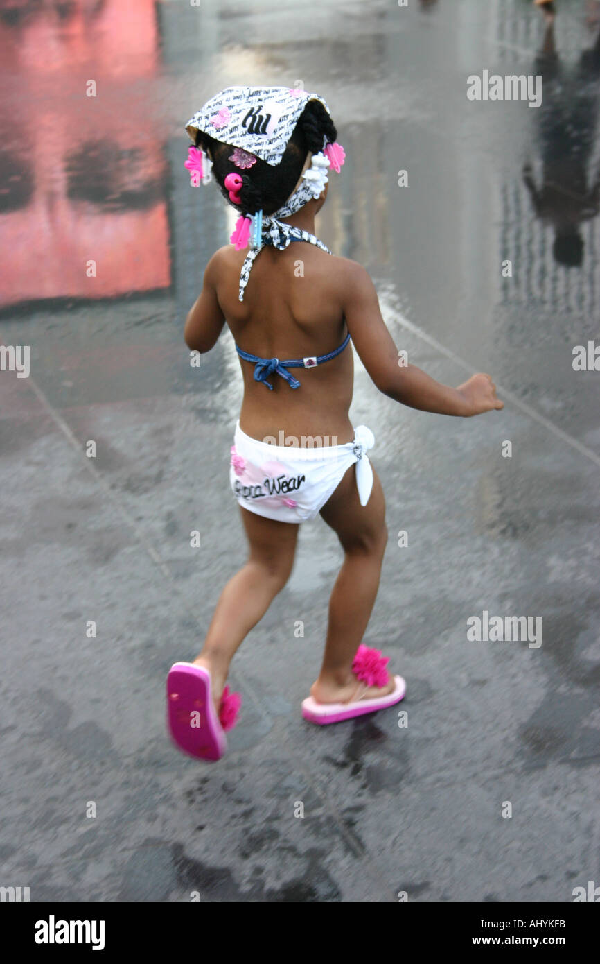 080c2847506d2 Young girl wearing a bikini and bandana and pink flip flops running around  - Stock Image