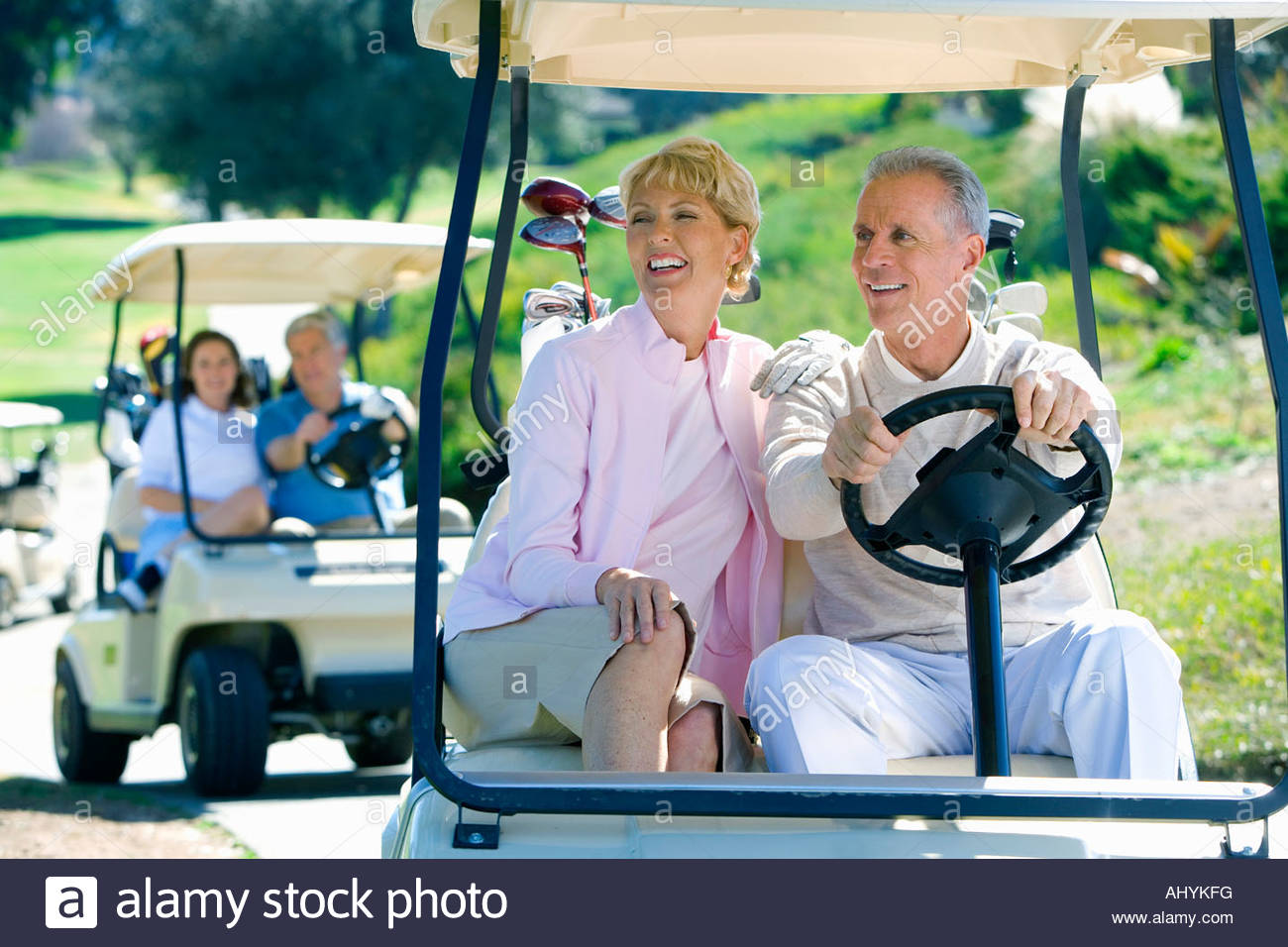 Two mature couples driving golf buggies along golf course pathway, focus on couple in foreground, smiling - Stock Image