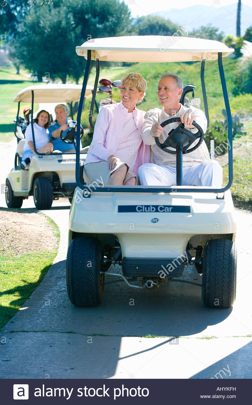 Two mature couples driving golf buggies along golf course pathway, smiling - Stock Image