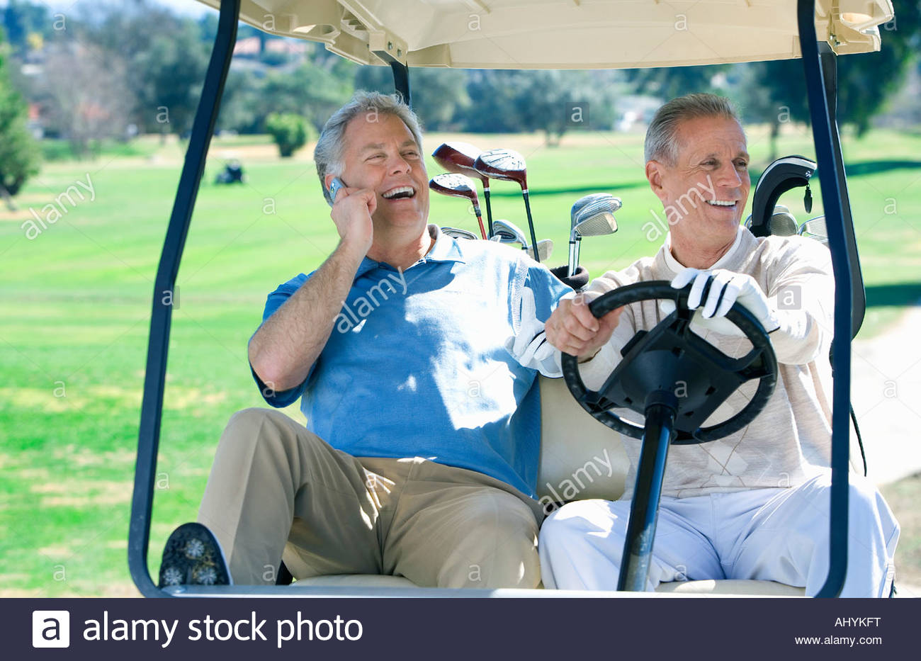 Two mature men sitting in golf buggy on golf course, one man driving, other man using mobile phone, smiling, front - Stock Image
