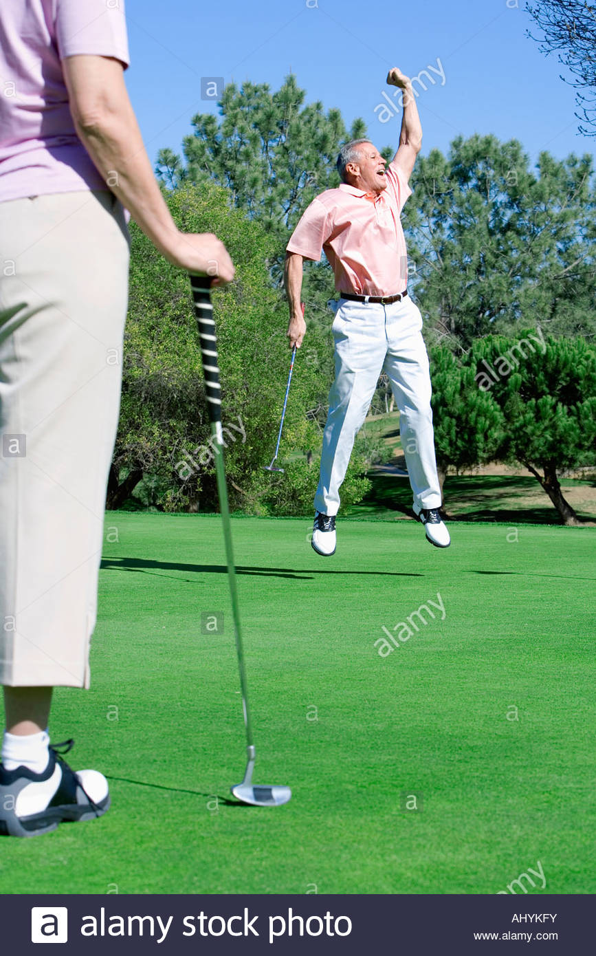 Mature couple playing golf, man punching air in delight at successful putt, woman watching in foreground - Stock Image