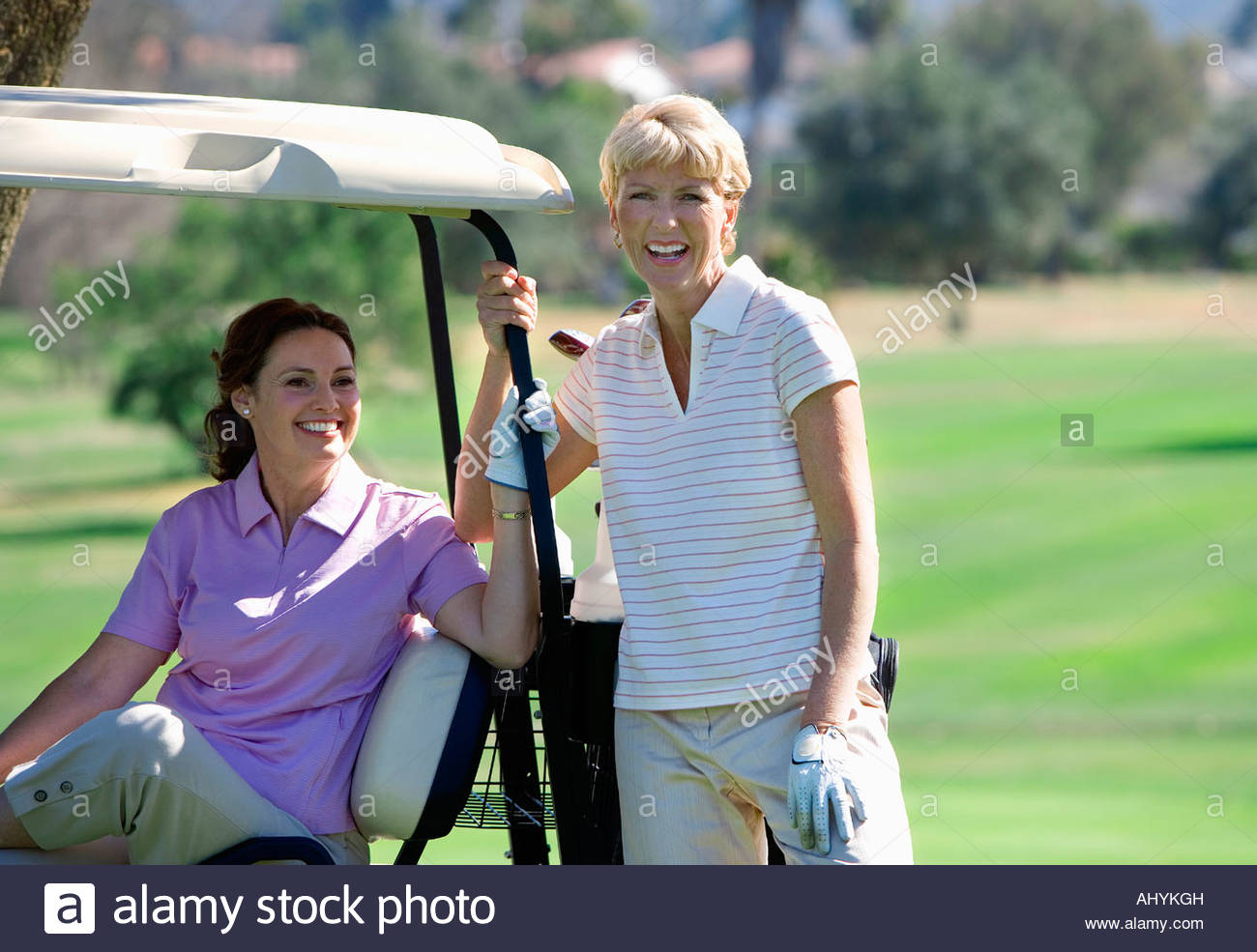 Two mature women posing on golf course, brunette sitting in golf buggy, blonde standing beside her, smiling, portrait - Stock Image