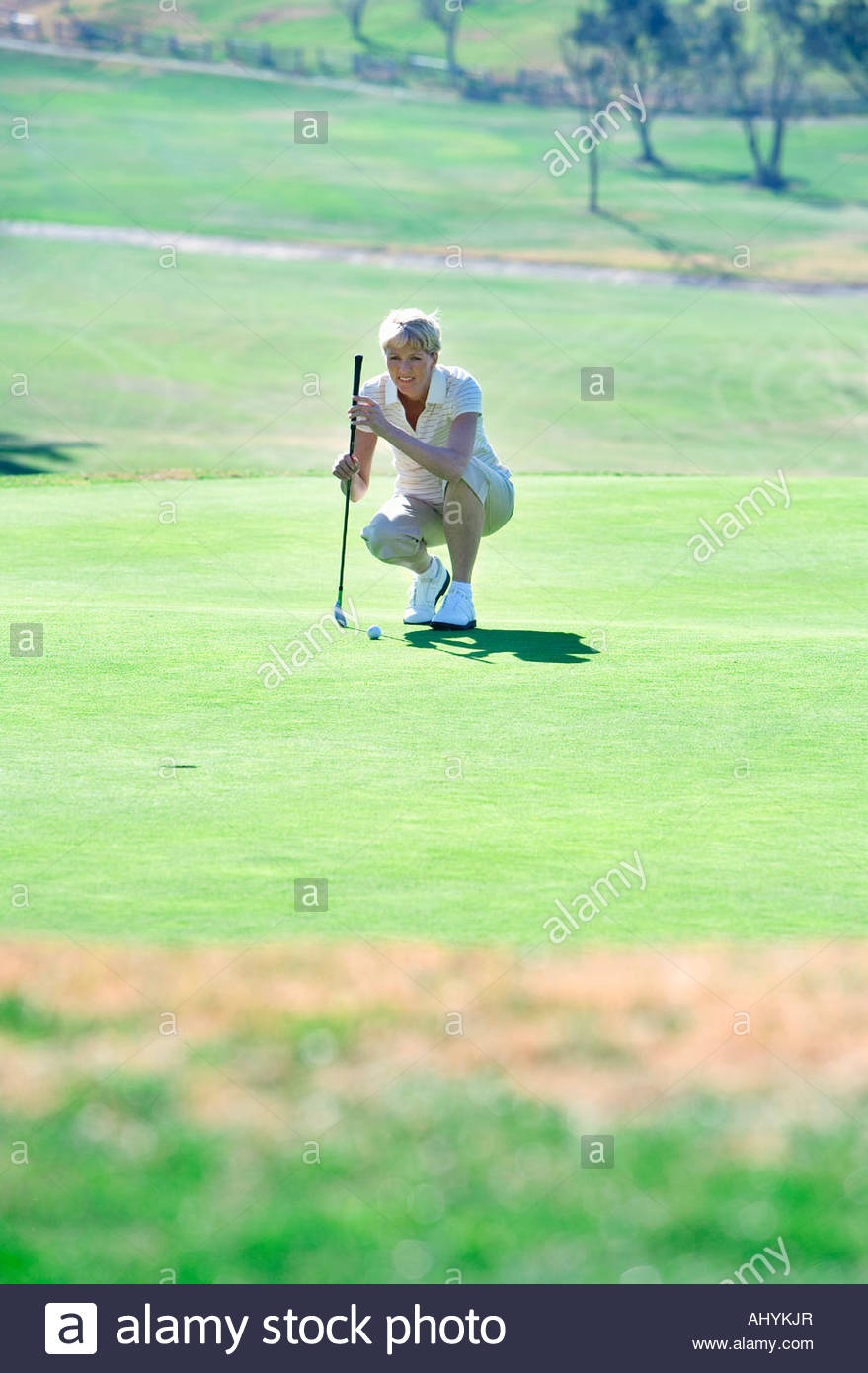 Mature woman lining up putting shot on green in mid-distance, holding putter, crouching, focus on background - Stock Image