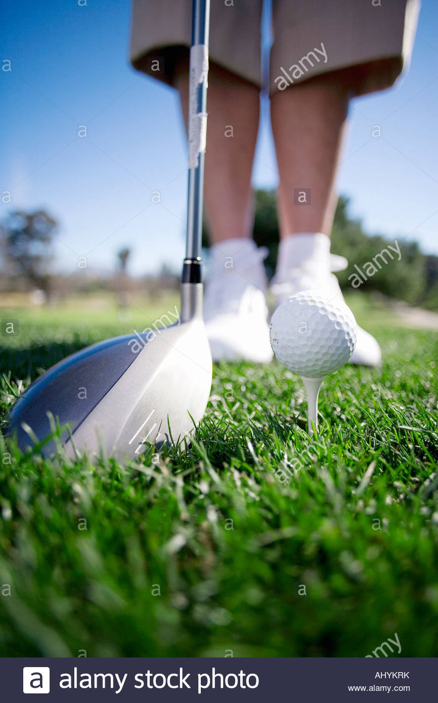 Mature woman preparing to tee off with driver on golf course, close-up, low section surface level - Stock Image