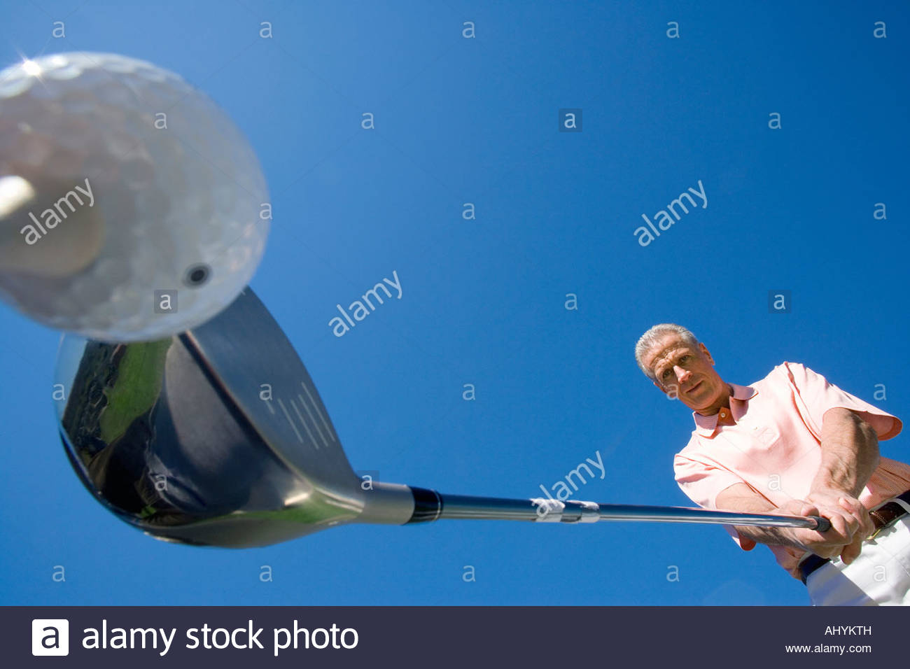 Mature man preparing to tee off on golf course, holding driver, close-up, upward view wide angle - Stock Image