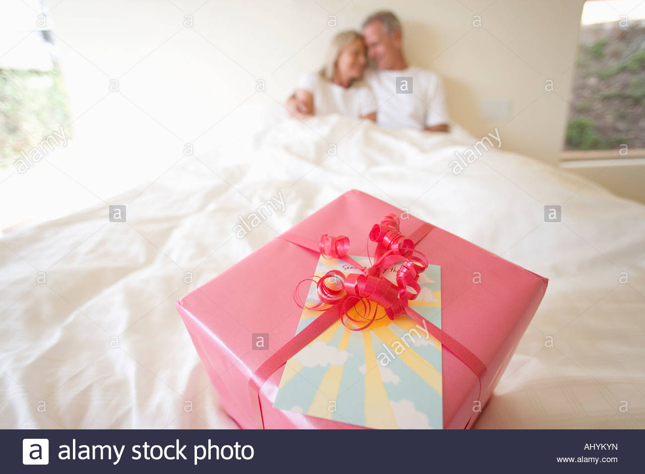 Mature Couple Sitting Upright In Bed Focus On Birthday Gift Wrapped Pink Wrapping Paper And Red Ribbon Foreground