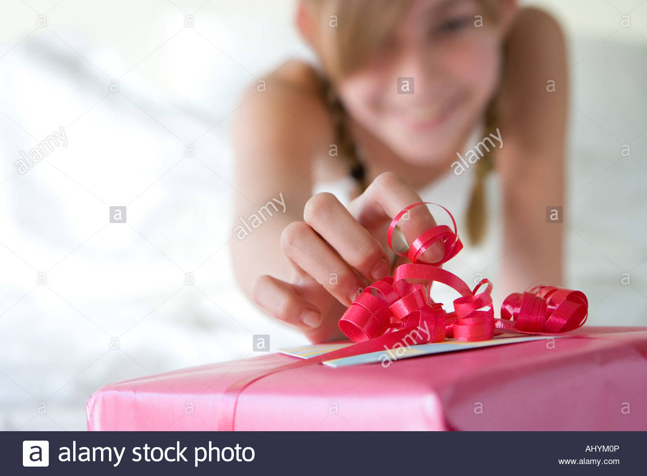 Girl  touching red ribbon with finger on pink birthday gift, smiling, front view, focus on foreground - Stock Image