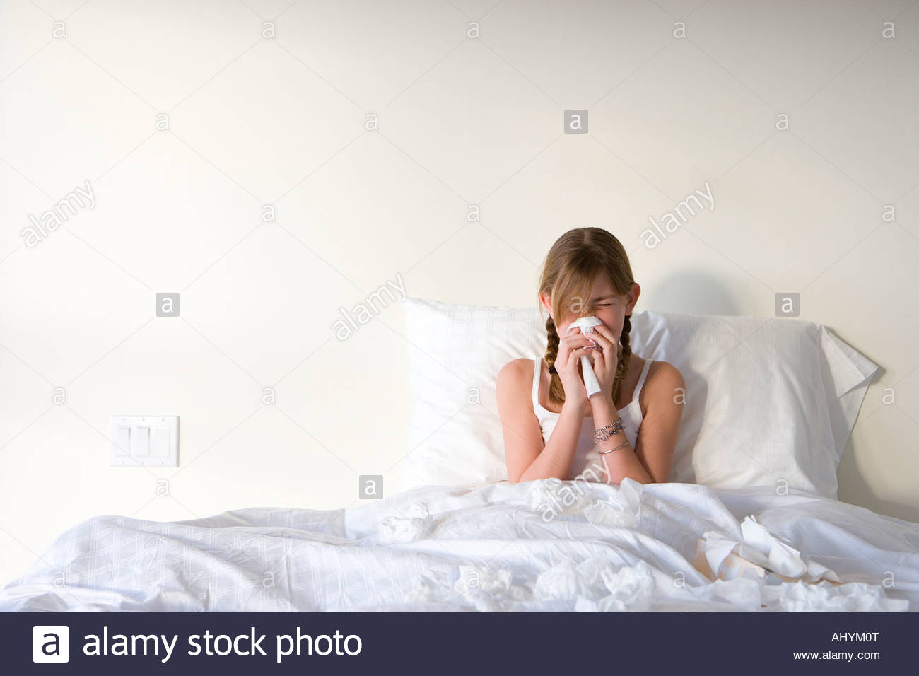 Girl  sitting upright in bed, blowing nose with handkerchief, front view - Stock Image