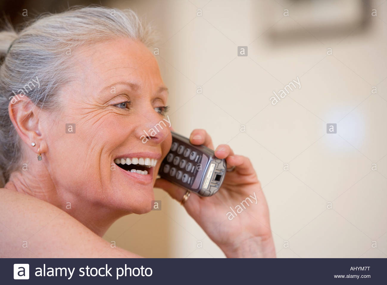 Senior woman using cordless phone, laughing, close-up, side view - Stock Image