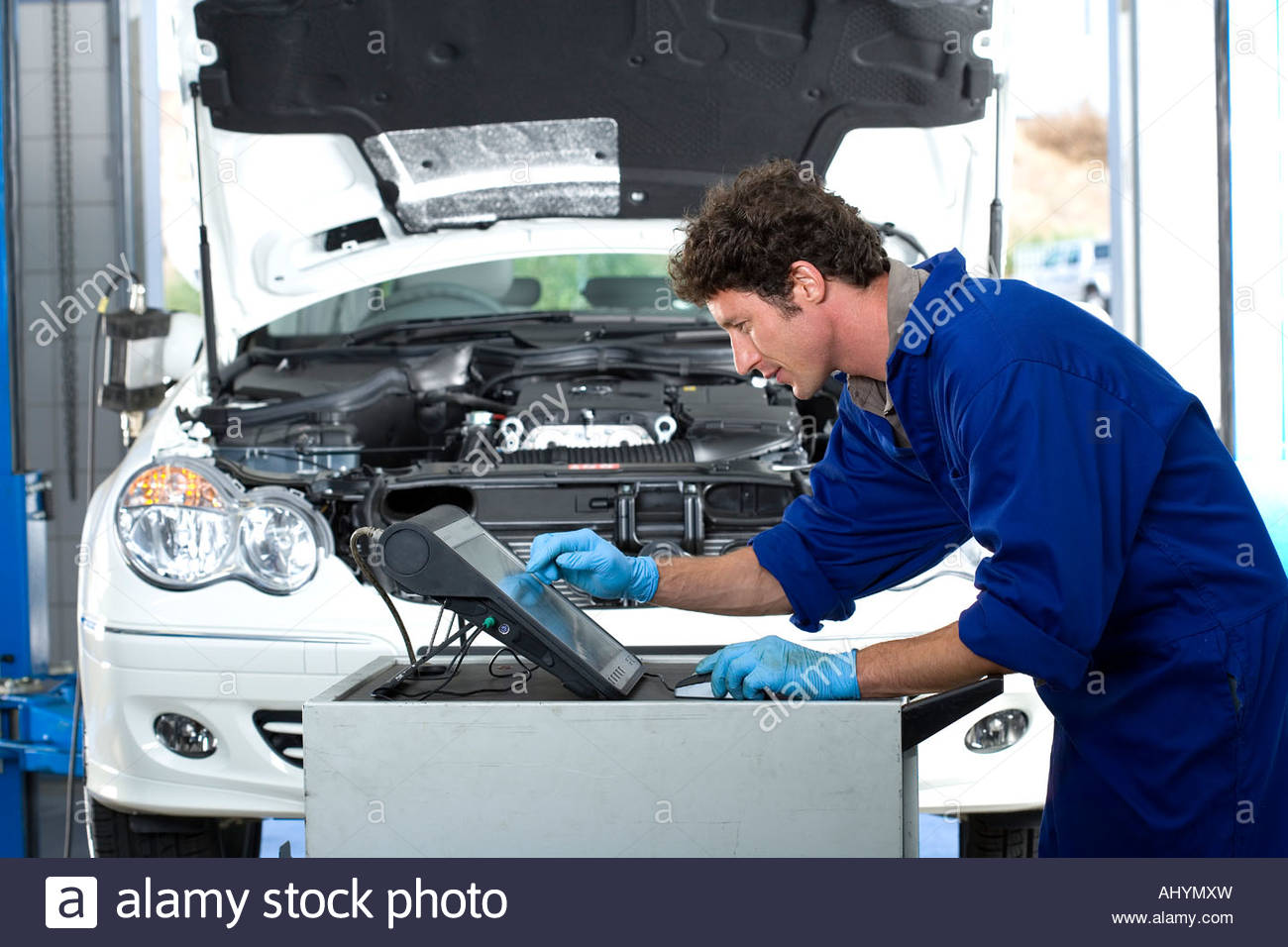 Male Car Mechanic In Blue Overalls Using Computer In