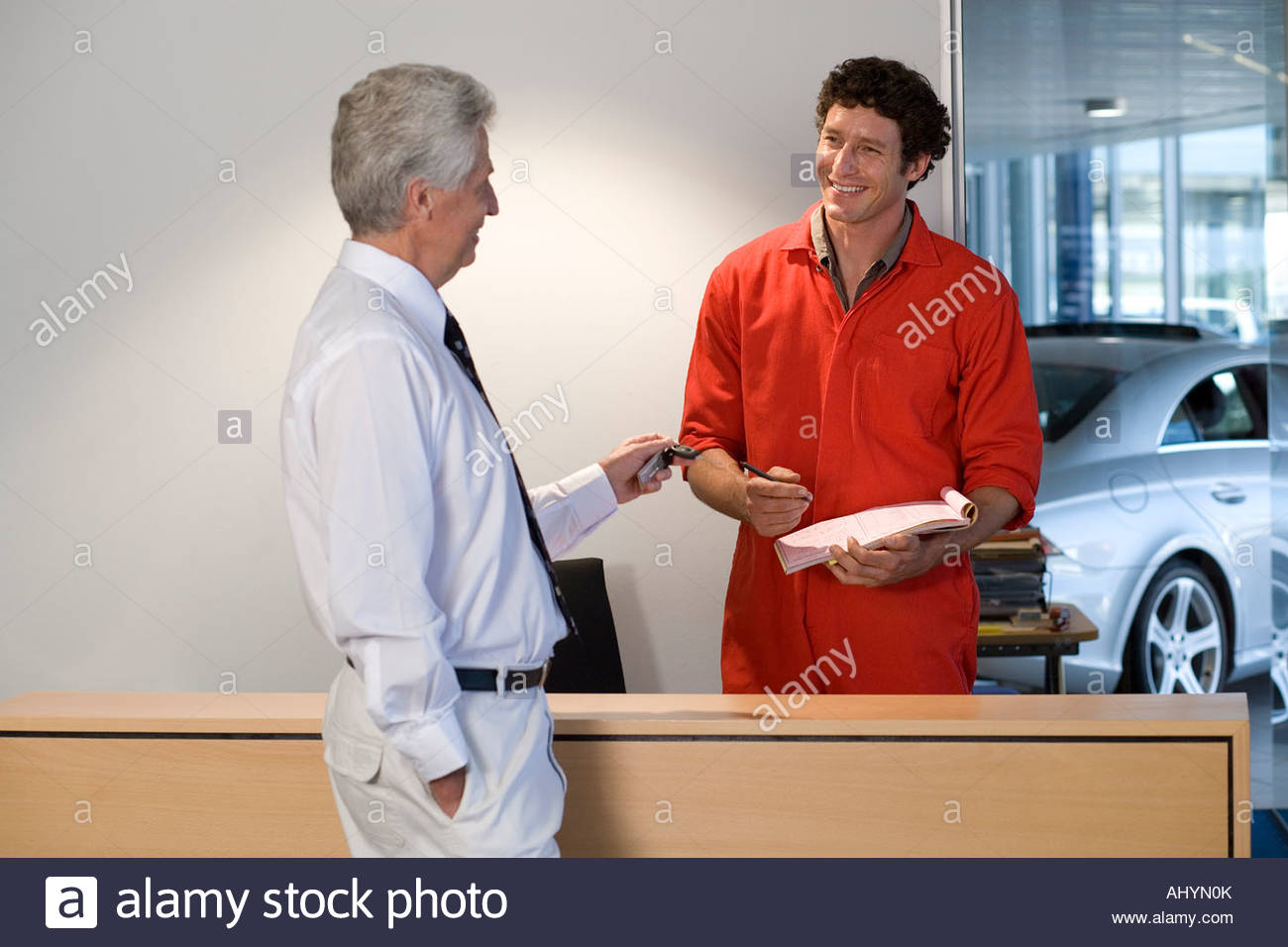 Male customer paying with credit card at auto repair shop reception counter, car mechanic, in red overalls, serving - Stock Image
