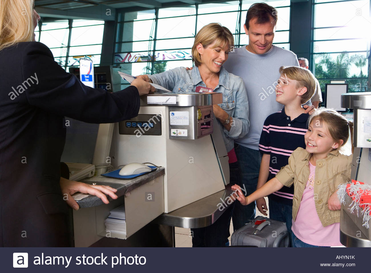 Family checking in at airport check-in counter, woman passing tickets to female airline check-in attendant, smiling - Stock Image