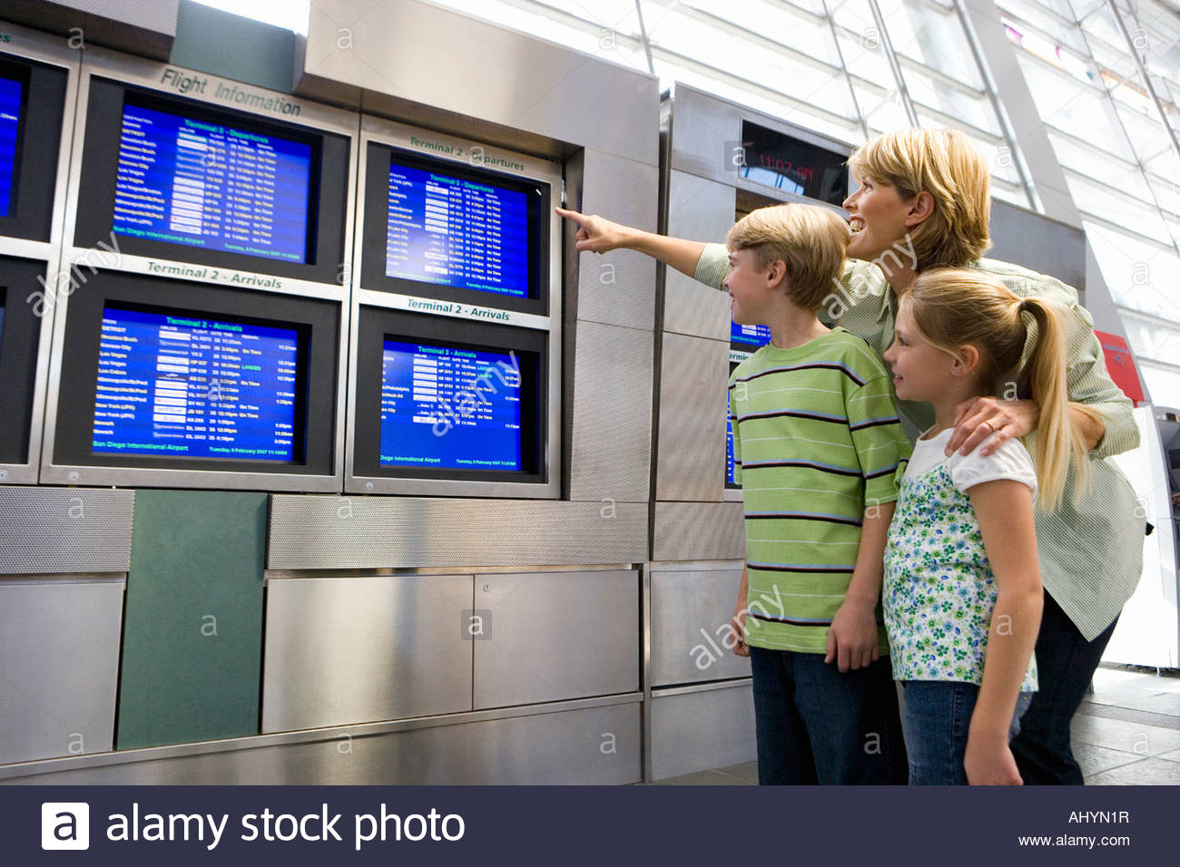 Mother and children looking at flight information screen in airport departure lounge, woman pointing, smiling - Stock Image