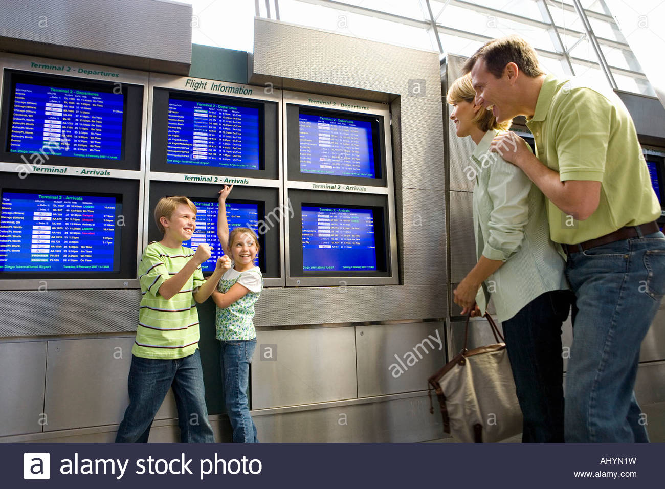 Parents looking at excited children  pointing at flight information screen in airport departure lounge - Stock Image