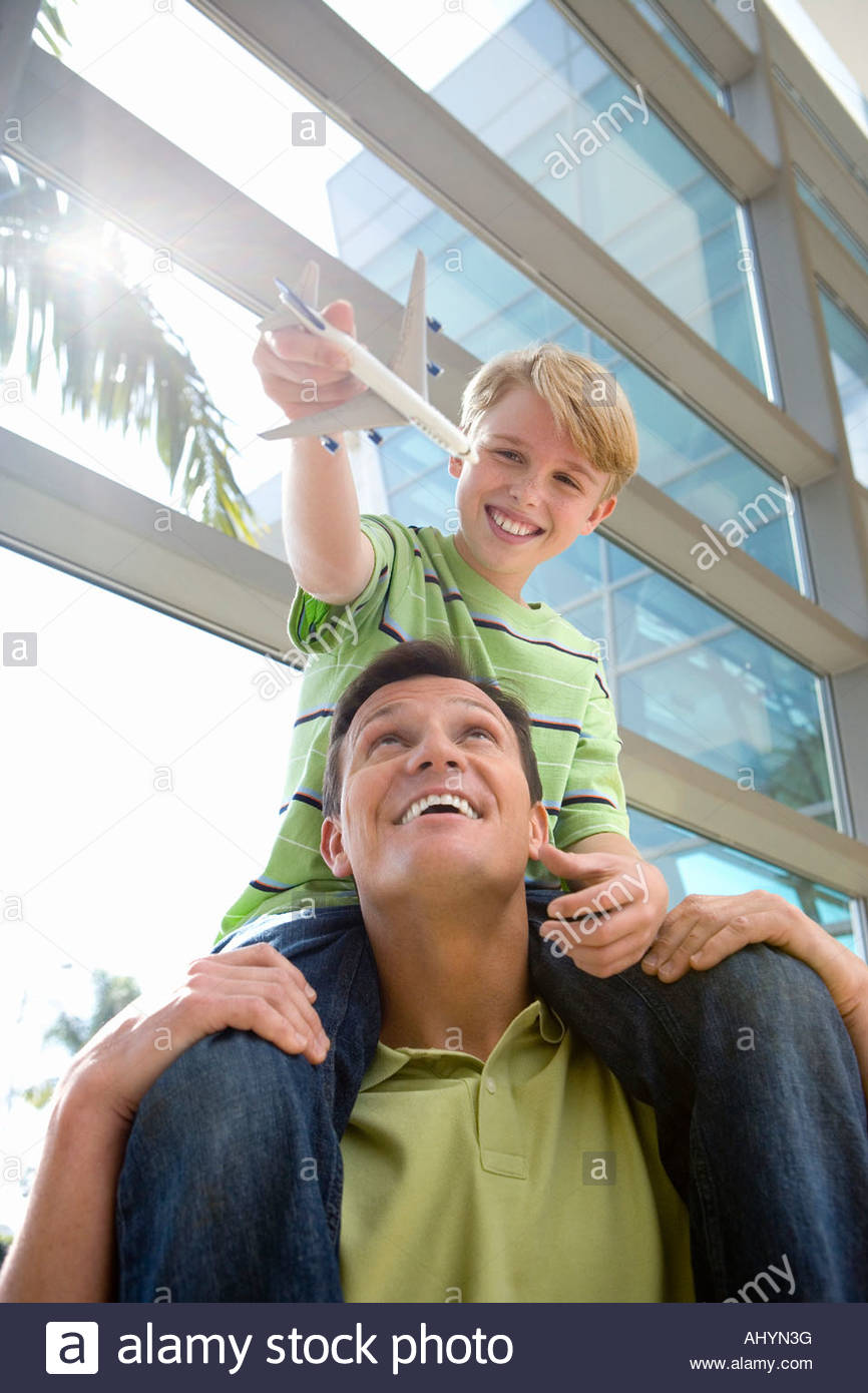 Father carrying son  on shoulders in airport, boy holding toy aeroplane, smiling, front view, low angle view lens Stock Photo
