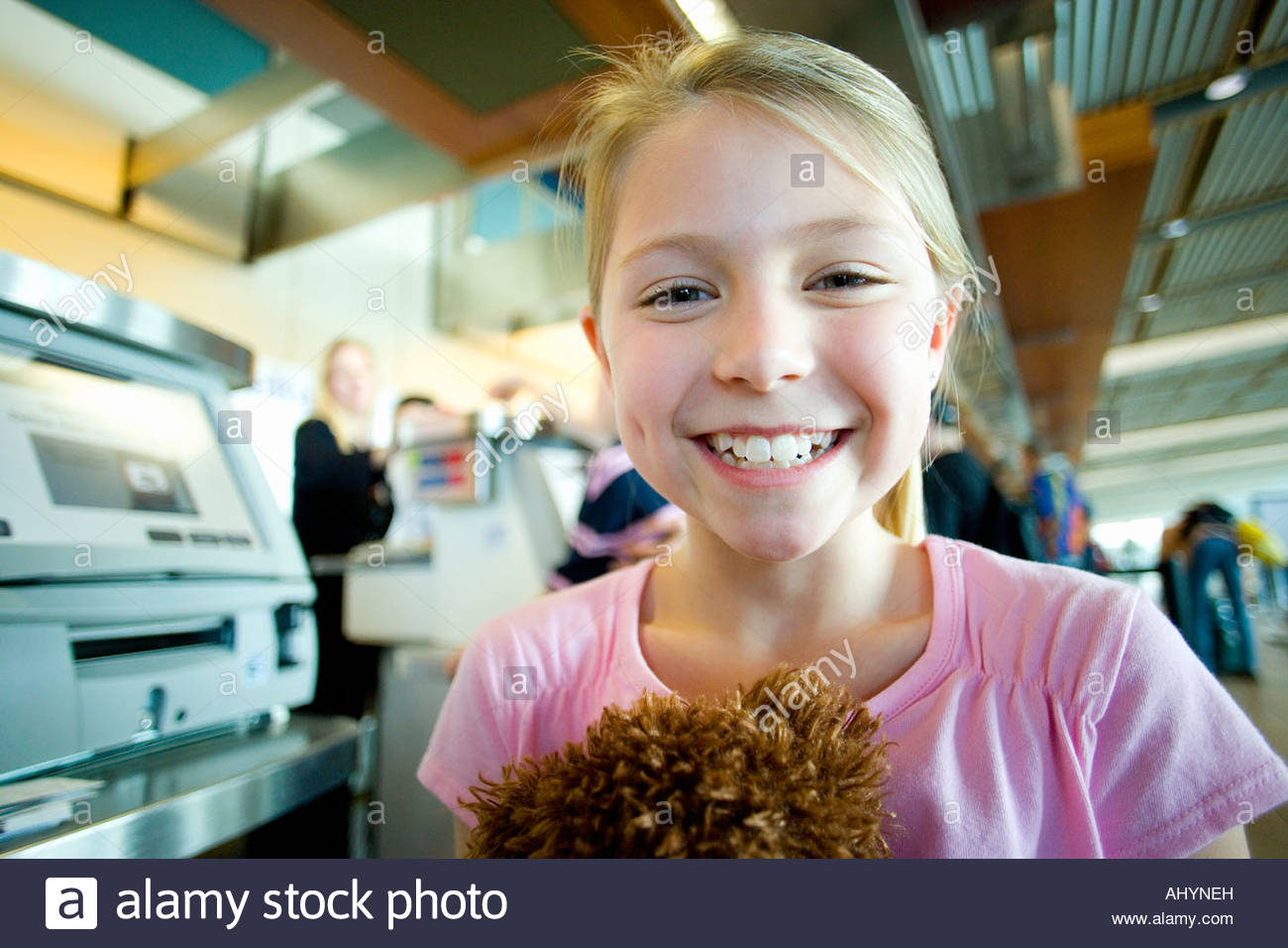 Blonde girl  standing near airport check-in counter, holding soft toy, smiling, close-up, portrait, focus on foreground - Stock Image