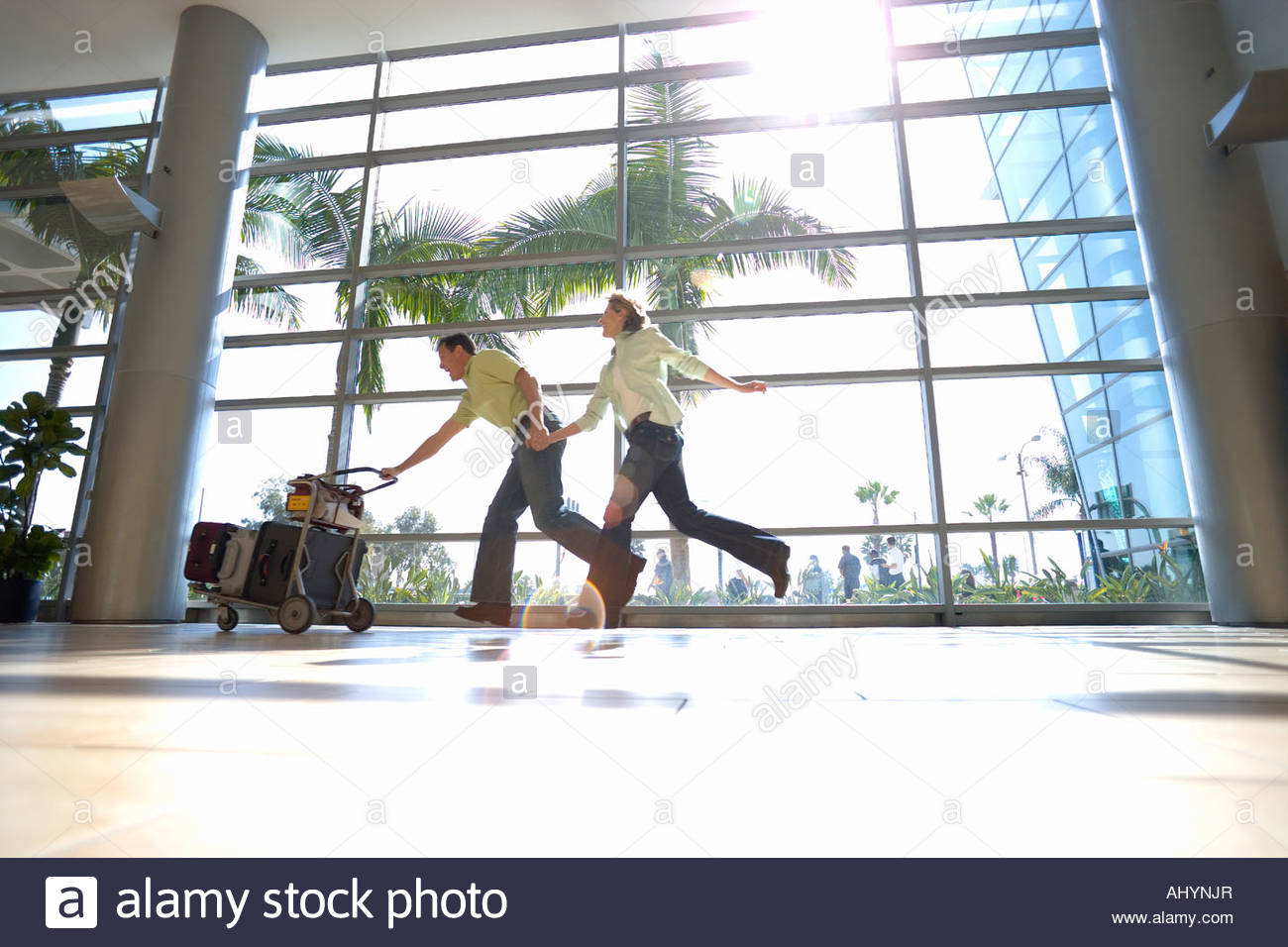 Couple running through airport with luggage trolley in tow, man leading, holding hands, smiling, side view surface - Stock Image