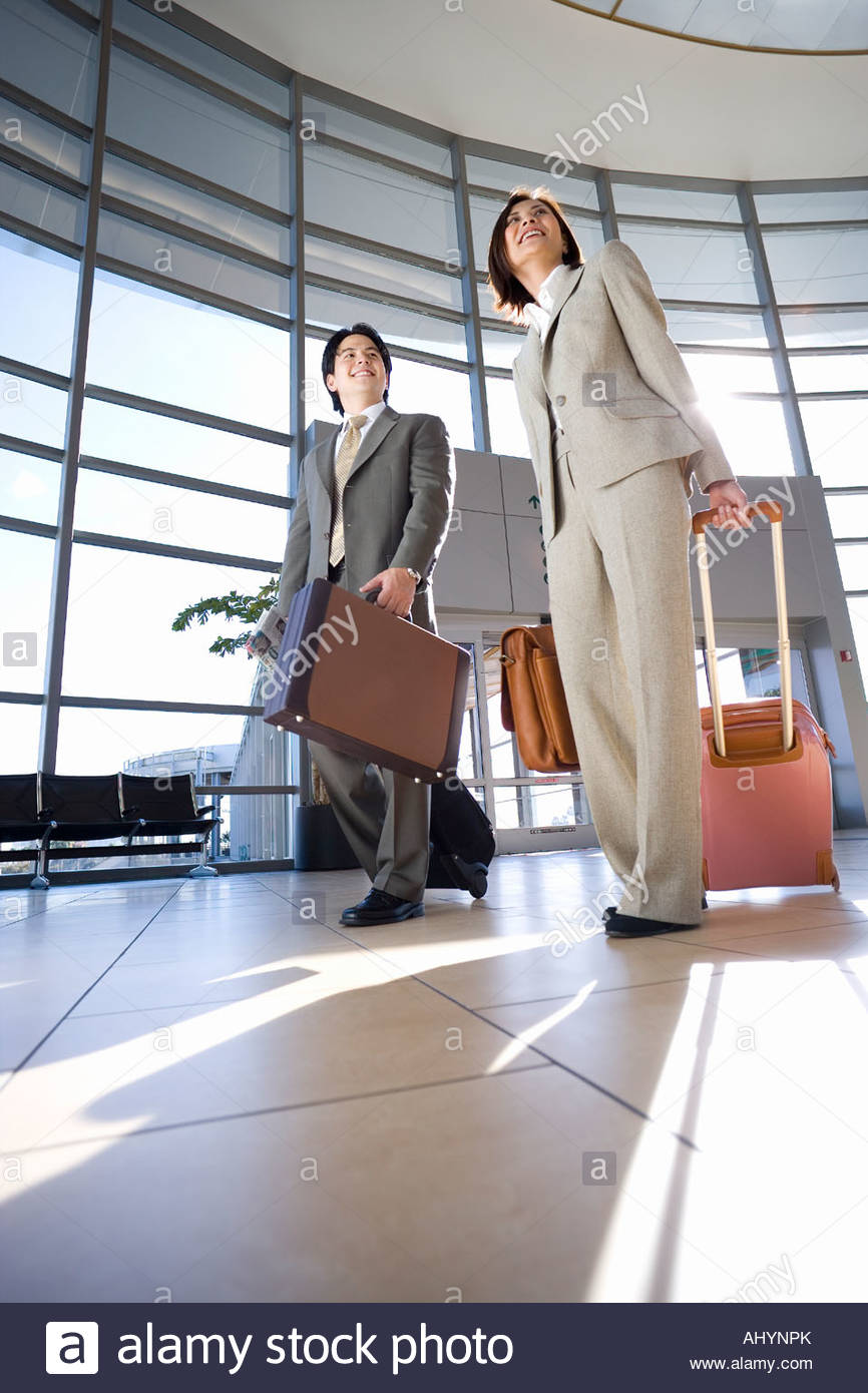 Businessman and woman walking with luggage in tow in airport, building entrance in background surface level - Stock Image