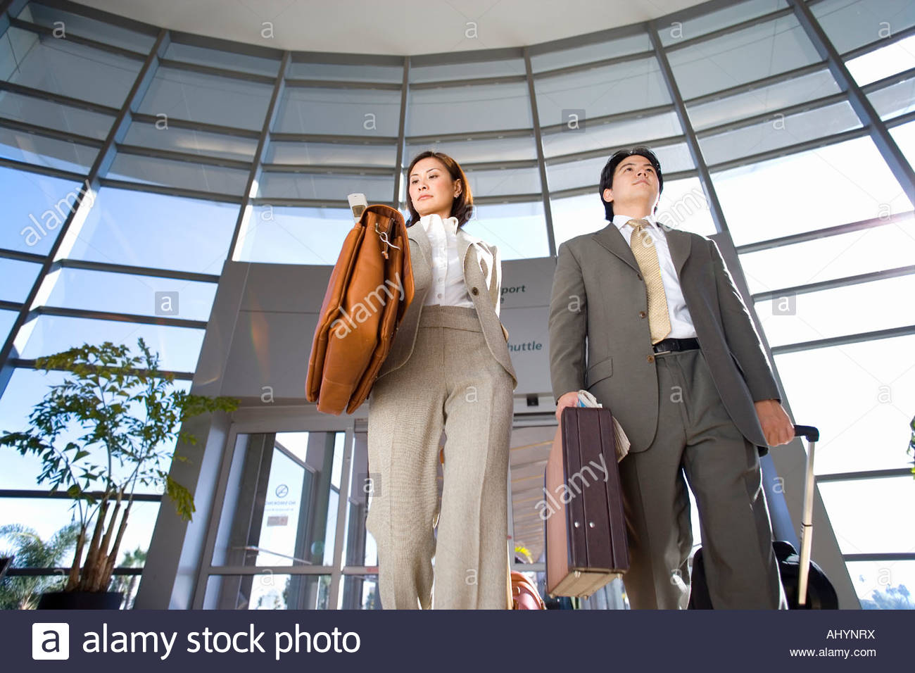 Businessman and woman walking with luggage in tow in airport, building entrance in background, front view, low angle - Stock Image