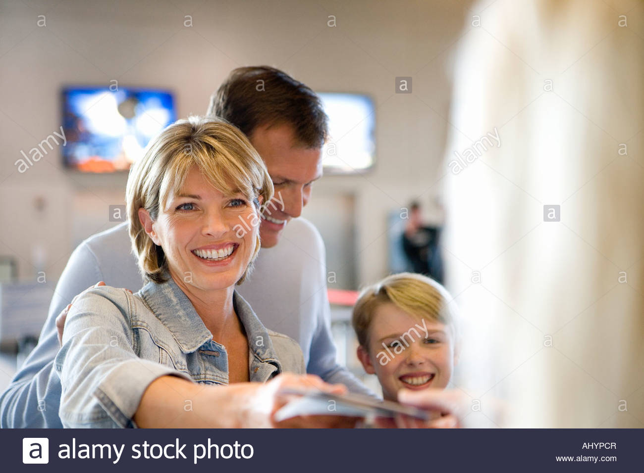 Family standing at airport check-in desk, woman handing passports to check-in attendant, smiling differential focus - Stock Image