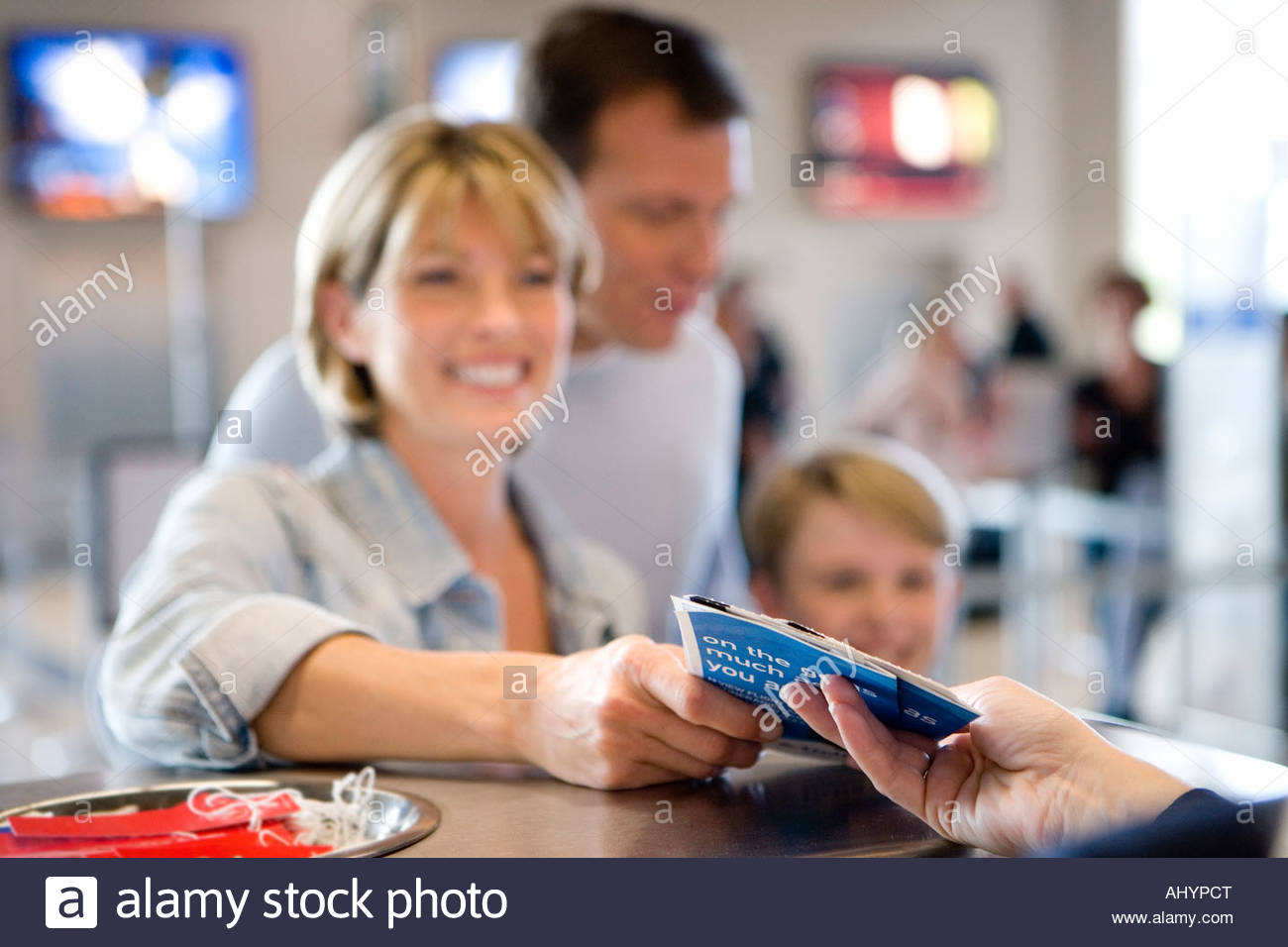 Family standing at airport check-in desk, woman receiving boarding passes from check-in attendant, smiling, focus - Stock Image