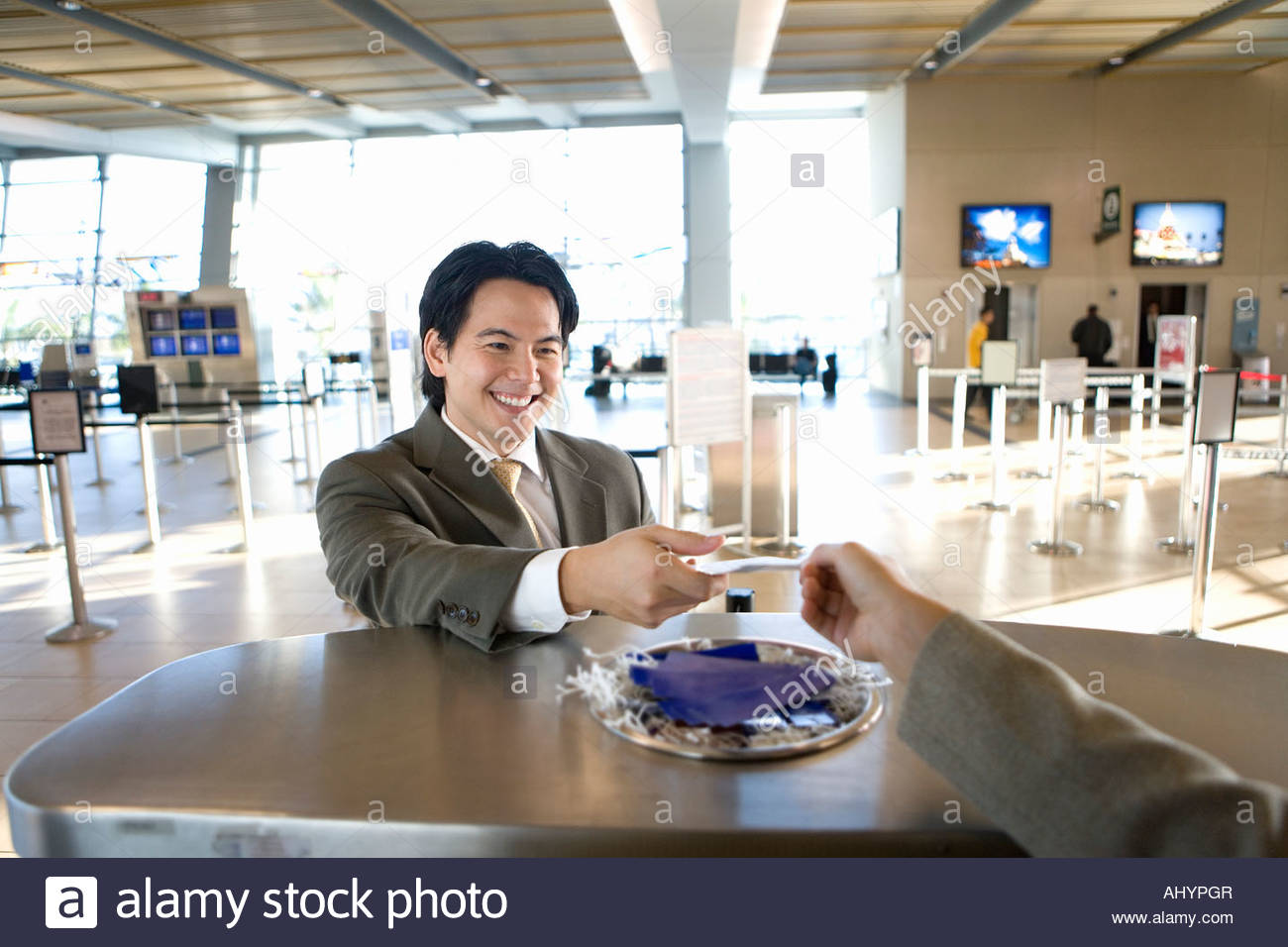 Businessman checking in at airport, receiving boarding pass from check-in attendant, view from behind check-in desk - Stock Image