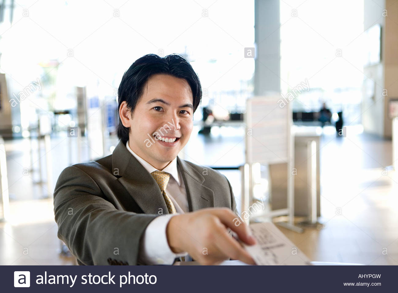 Businessman checking in at airport, receiving boarding pass from check-in attendant, smiling, portrait, behind check - Stock Image