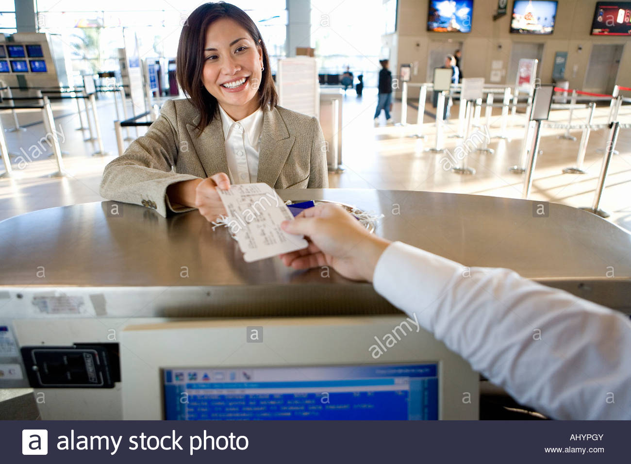 Businesswoman checking in at airport, receiving boarding pass from check-in attendant, smiling, portrait, behind - Stock Image