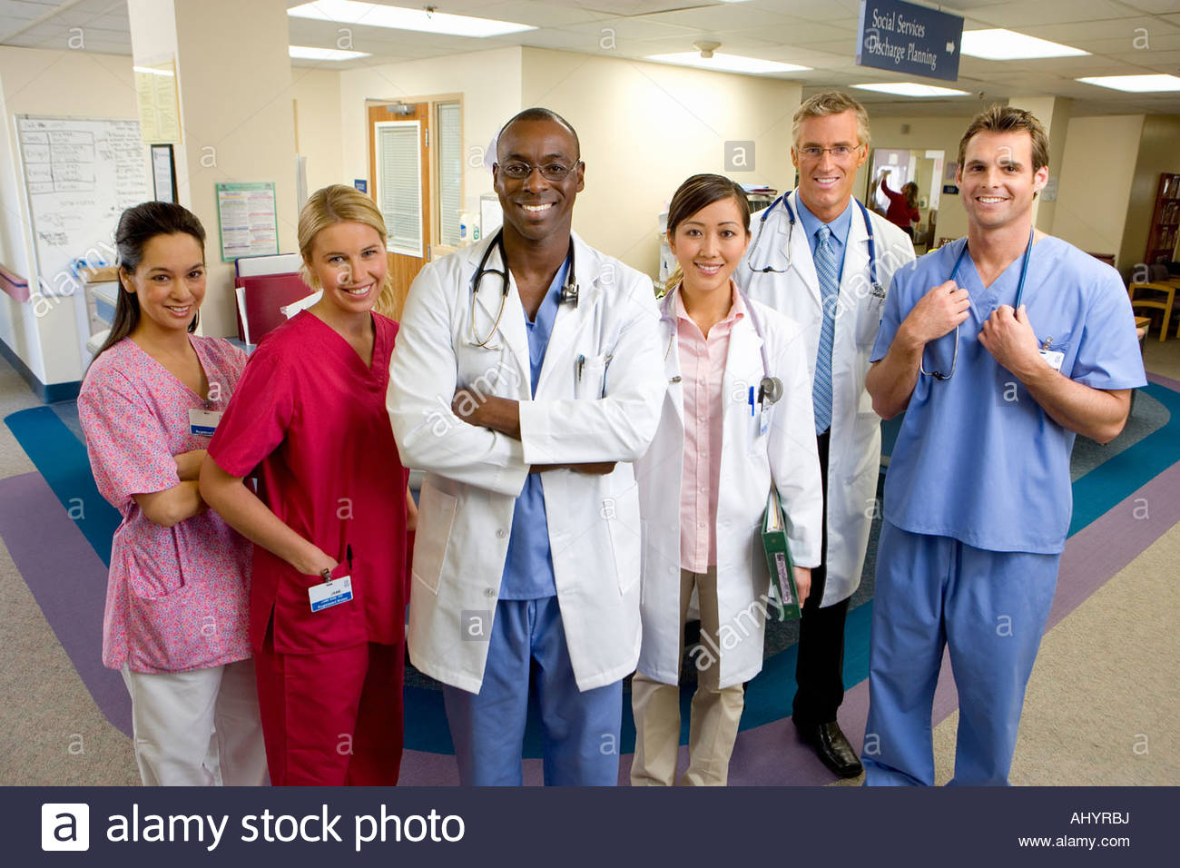 Hospital staff standing in ward, smiling, portrait - Stock Image
