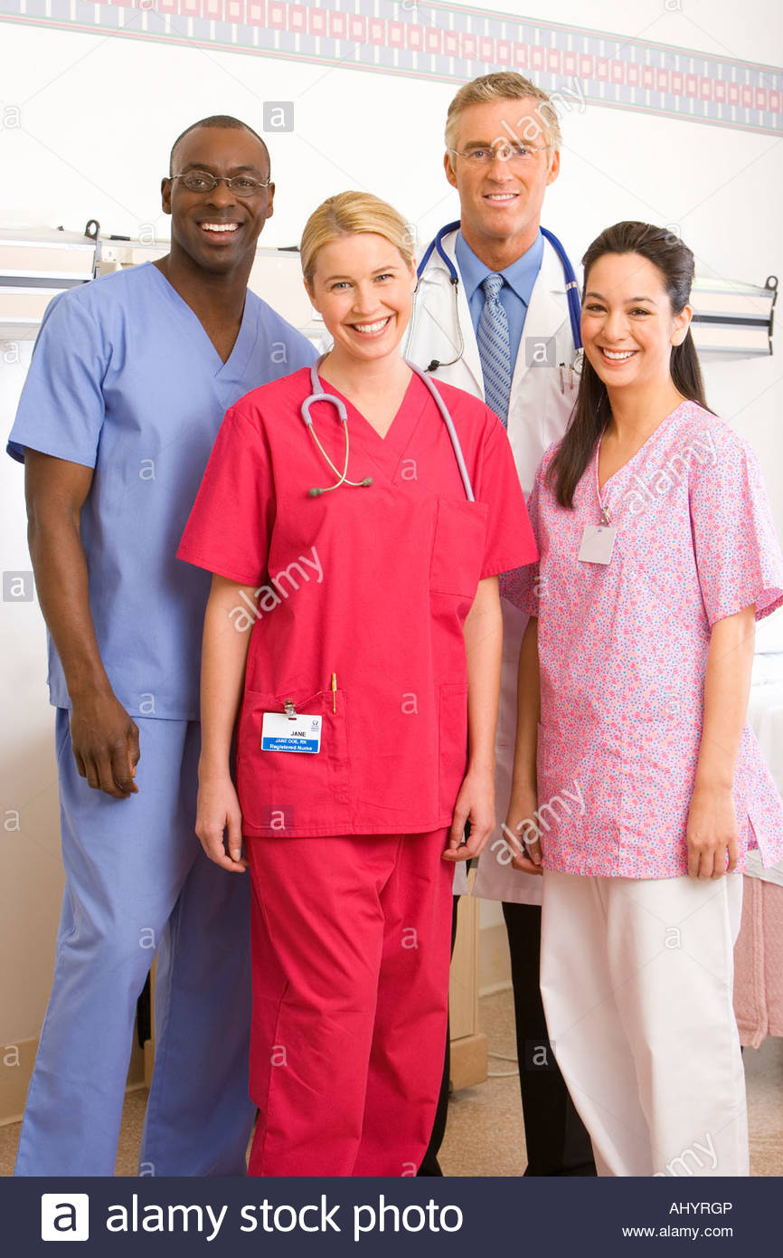 Four hospital staff standing in ward, smiling, portrait - Stock Image