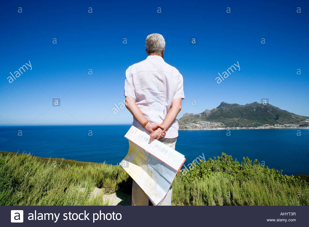 South Africa, Cape Town, senior man holding map, looking out to sea, rear view - Stock Image